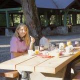 Mujer joven que goza del desayuno al aire libre Imágenes de archivo libres de regalías