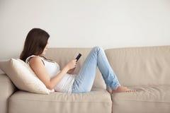 Mujer joven que goza del libro interesante que se sienta en el sofá, leyendo Imagen de archivo libre de regalías