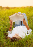 Mujer joven que goza del libro que lee al aire libre Fotos de archivo