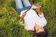 Mujer joven que goza del libro que lee al aire libre Imagen de archivo libre de regalías
