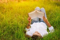 Mujer joven que goza del libro que lee al aire libre Fotografía de archivo