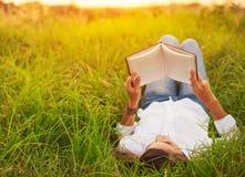 Mujer joven que goza del libro que lee al aire libre Fotos de archivo libres de regalías