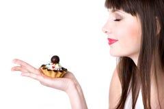 Mujer joven que goza del olor de la torta Imagen de archivo