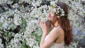 Mujer joven que goza del olor del árbol floreciente metrajes