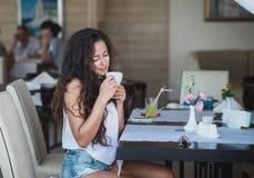 Mujer joven que goza del olor del café Imagen de archivo libre de regalías