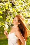 Mujer joven que goza del olor del flor del cerezo Fotos de archivo