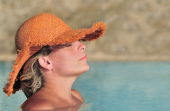 Mujer joven que goza del sol en la piscina Imagen de archivo libre de regalías