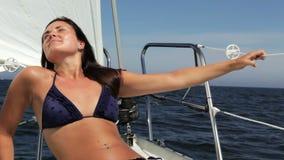 Mujer joven que goza del sol y del mar que navegan un día soleado en el archipiélago de Estocolmo, Suecia almacen de video