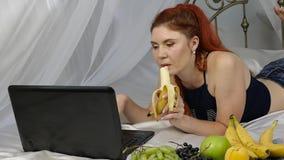 Mujer joven que goza en una cama, usando el ordenador portátil y comiendo un plátano en casa por la mañana Cámara lenta almacen de video