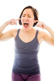 Mujer joven que grita con los fingeres en sus oídos Foto de archivo libre de regalías