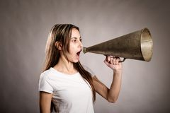 Mujer joven que grita con un megáfono viejo Imagen de archivo libre de regalías