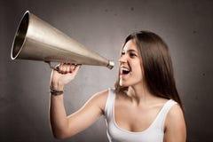 Mujer joven que grita con un megáfono viejo Imágenes de archivo libres de regalías