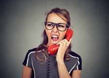 Mujer joven que grita en el teléfono rojo fotografía de archivo