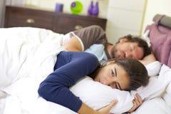 Mujer joven que grita en la cama desesperada Imagen de archivo libre de regalías