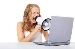 Mujer joven que grita en la computadora portátil Fotografía de archivo