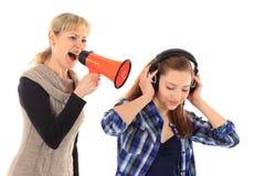 Mujer joven que grita en su hija con un megáfono en blanco Fotos de archivo libres de regalías
