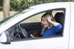 Mujer joven que grita mientras que conduce el Ca imagenes de archivo