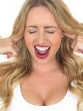 Mujer joven que grita no escuchando con los fingeres en oídos Fotos de archivo libres de regalías