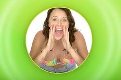 Mujer joven que grita o que grita a través de un anillo de goma grande verde Foto de archivo