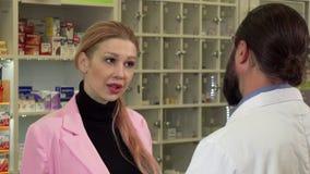 Mujer joven que habla con el farmacéutico, haciendo compras en la droguería metrajes