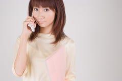 Mujer joven que habla con el teléfono móvil Imágenes de archivo libres de regalías
