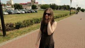 Mujer joven que habla en el Smart-teléfono mientras que camina al aire libre Lanzamiento constante de la leva almacen de video