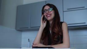 Mujer joven que habla en el smartphone y que sonríe en la cocina almacen de video