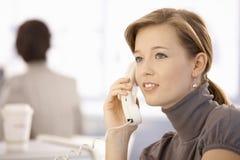 Mujer joven que habla en el teléfono Imágenes de archivo libres de regalías