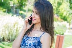 Mujer joven que habla en el teléfono Imagen de archivo libre de regalías
