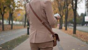 Mujer joven que habla en el teléfono que camina abajo de la calle almacen de metraje de vídeo