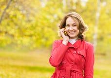 Mujer joven que habla en el teléfono celular Foto de archivo libre de regalías