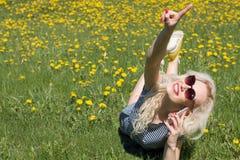 Mujer joven que habla en el teléfono en la hierba Concepto del verano Foto de archivo libre de regalías