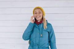 Mujer joven que habla en el teléfono la mujer en amarillo hizo punto el sombrero y una chaqueta azul usando el teléfono elegante  Imagen de archivo