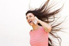Mujer joven que habla en el teléfono móvil con soplar del pelo Imagen de archivo libre de regalías