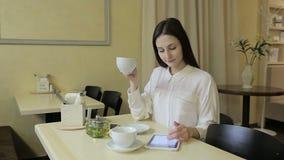 Mujer joven que habla en el teléfono móvil en café almacen de video