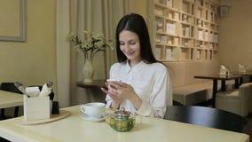 Mujer joven que habla en el teléfono móvil en café almacen de metraje de vídeo
