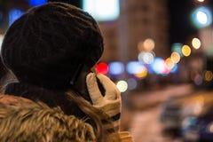 Mujer joven que habla en el teléfono móvil en la noche en invierno Imagenes de archivo