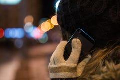 Mujer joven que habla en el teléfono móvil en la noche en invierno Fotografía de archivo libre de regalías