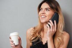 Mujer joven que habla en el teléfono móvil mientras que sostiene la taza de café Imágenes de archivo libres de regalías