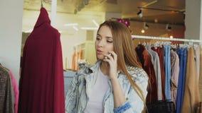 Mujer joven que habla en el teléfono móvil y que elige la ropa en boutique Ella está mirando el puente hecho punto, tocándolo y almacen de metraje de vídeo