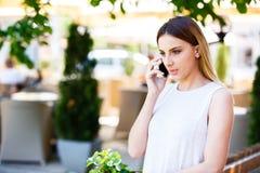 Mujer joven que habla en el teléfono mientras que coloca el jardín cercano del ` s del café Fotografía de archivo libre de regalías