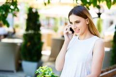 Mujer joven que habla en el teléfono mientras que coloca el jardín cercano del ` s del café Foto de archivo libre de regalías