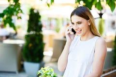 Mujer joven que habla en el teléfono mientras que coloca el jardín cercano del ` s del café Imagenes de archivo