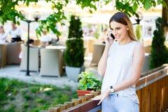 Mujer joven que habla en el teléfono mientras que coloca el jardín cercano del ` s del café Imágenes de archivo libres de regalías