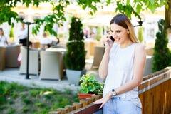 Mujer joven que habla en el teléfono mientras que coloca el jardín cercano del ` s del café Fotos de archivo libres de regalías