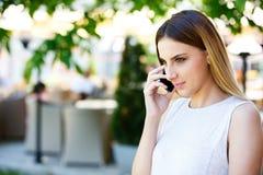 Mujer joven que habla en el teléfono mientras que coloca el jardín cercano del ` s del café Imagen de archivo