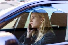 Mujer joven que habla en el teléfono mientras que conduce el coche Imágenes de archivo libres de regalías