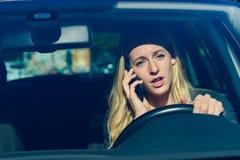 Mujer joven que habla en el teléfono mientras que conduce el coche Imagen de archivo libre de regalías