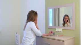 Mujer joven que habla en el teléfono mientras que aplica maquillaje delante del espejo del hotel almacen de metraje de vídeo