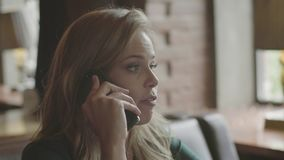 Mujer joven que habla en el teléfono que se sienta en restaurante almacen de video